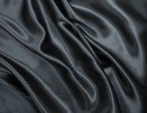 Släta elegant svart silke- eller satängtextur som abstrakt backgroun Royaltyfria Foton