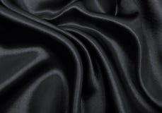 Släta elegant svart silke- eller satängtextur som abstrakt backgroun Arkivbilder