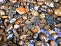 Släta stenar i vatten Arkivfoto