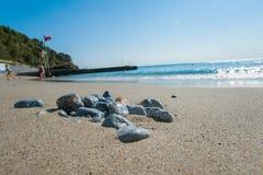 Släta stenar på stranden, havet vilar arkivbild