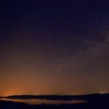 Släta yttersida av sjön på bakgrund den stjärnklara himlen Arkivbilder