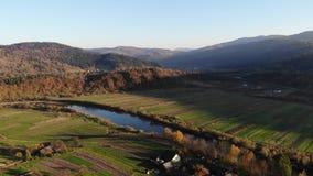 Slätt flyg över den gamla byn och floden i den Carpathian dalen, Ukraina Hösttid, flyg- sikt arkivfilmer