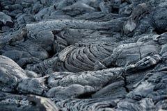 Slätt och att bölja yttersida av djupfryst pahoehoelava Djupfryst lava som in rynkas gobeläng-som veck och rullar som liknar det  Royaltyfri Fotografi