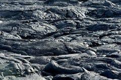 Slätt och att bölja yttersida av djupfryst pahoehoelava Djupfryst lava som in rynkas gobeläng-som veck och rullar som liknar det  Royaltyfri Foto