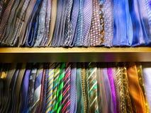 Slätt och mönstrade designer av slipsar på hylla Arkivbilder