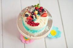 Slå kakan med kräm och bär på en vit trätabell Arkivfoton