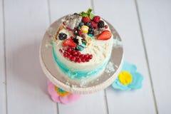 Slå kakan med kräm och bär på en vit trätabell Royaltyfri Fotografi