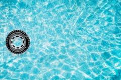 Slå samman flötet, cirkeln som svävar i en uppfriskande blå simbassäng med palmträdbladskuggor i vatten Arkivbild