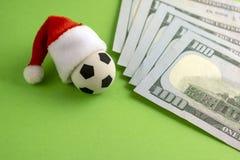 Slå vad för sportar för nytt år Souvenirfotbollboll i en röd Santa Claus hatt bredvid dollar på en grön bakgrund Begreppet av a fotografering för bildbyråer