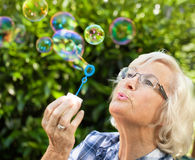 slående bubblapensionärkvinna Arkivbild