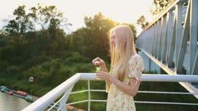 slående bubblor soap kvinnan Sidosikt av den nätta kvinnan som blåser såpbubblor, medan stå på den fot- bron lager videofilmer