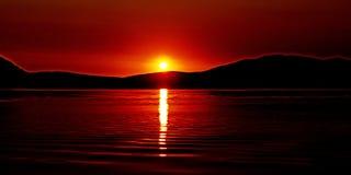 Slående karmosinröd soluppgångseascape med vattenreflexioner Royaltyfri Foto
