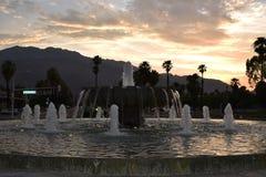 Slående sikt av en springbrunn på solnedgången fotografering för bildbyråer