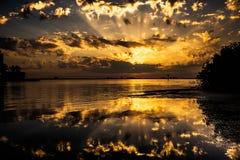 Slående solljussolnedgång som är härlig på strandvattenreflexionen Arkivbild