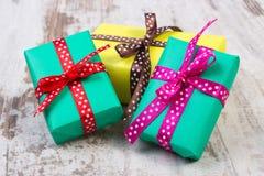Slågna in färgrika gåvor för jul eller annan beröm på gammal vit planka Royaltyfria Foton