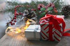 slågna in gåvor Julklappar på den gamla trätabellen med det suddiga granträdet och girlanden i bakgrunden Arkivfoto