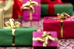 Slågna in gåvor med pilbågar i guld- och rött Arkivfoto