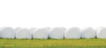 Slågna in staplade ensilagebaler ror, isolerad rund vit plast- Arkivfoton