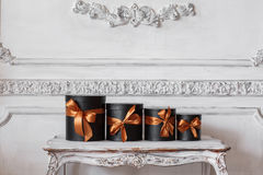 Slågna in svarta askar för gåva med band, som julklappar på en lyxig vit vägg för tabell planlägger basreliefstuckaturen Arkivfoton