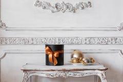 Slågna in svarta askar för gåva med band, som julklappar på en lyxig vit vägg för tabell planlägger basreliefstuckaturen Arkivbilder