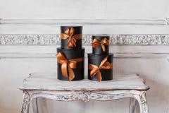 Slågna in svarta askar för gåva med band, som julklappar på en lyxig vit vägg för tabell planlägger basreliefstuckaturen Royaltyfri Foto