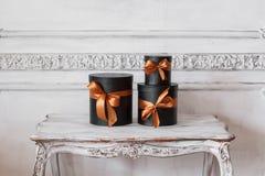 Slågna in svarta askar för gåva med band, som julklappar på en lyxig vit vägg för tabell planlägger basreliefstuckaturen Fotografering för Bildbyråer
