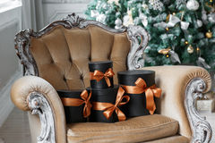 Slågna in svarta askar för gåva med band som julklappar på en stol Royaltyfri Bild