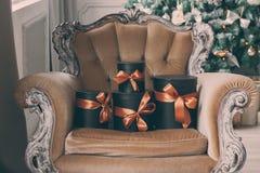 Slågna in svarta askar för gåva med band som julklappar på en stol Royaltyfri Foto