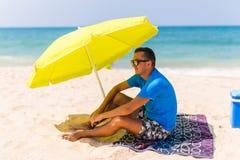 Slöa mannen i sol under det sol- paraplyet på handduken tyck om den lata tiden på stranden Arkivfoto