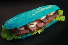 Slösa den bakade bagetten som fylls med union, kallt steknötkött för sallad Arkivfoto