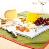 Slösa marmorportionmagasinet med ost, smällare, druvor, aprikors, brödpinnar och ostknivar Fotografering för Bildbyråer