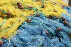 Slösa och gulna fisknät i fiskehamnen royaltyfri bild