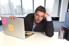 Slösad affärsman som arbetar i spänning på kontorsbärbar datordatoren som ser evakuerad royaltyfri bild
