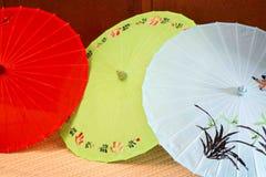 Slösar gör grön olika färger för japanska paraplyer som är röda, Arkivfoto