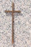 在一块优美的浅粉红色的花岗岩sl的一个简单的金纪念十字架 库存图片