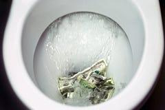 Sl?ta pengar ner toaletten arkivbilder
