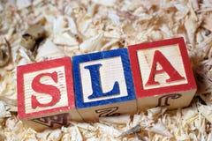 SLA text på träkvarteret arkivfoto