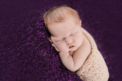 Slaap pasgeboren babymeisje op de violette achtergrond royalty-vrije stock foto