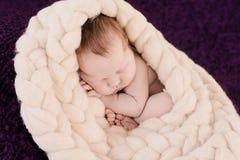 Slaap pasgeboren babymeisje op de violette achtergrond stock fotografie
