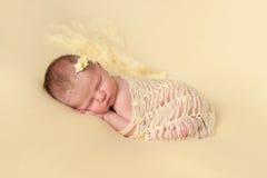 Slaap Pasgeboren die Babymeisje in Geel wordt ingewikkeld Royalty-vrije Stock Fotografie