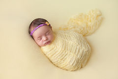 Slaap Pasgeboren die Babymeisje in Geel wordt ingewikkeld stock afbeeldingen