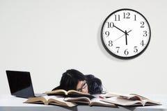In slaap student terwijl het bestuderen van tijd stock afbeelding