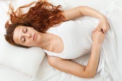 Slaap van het schoonheids de bed-haired meisje op wit hoofdkussen in bed Royalty-vrije Stock Foto