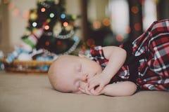 Slaapbaby dichtbij Kerstboom Stock Afbeelding