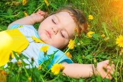 Slaapjongen op gras Stock Foto