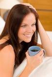 Slaapkamer - de jonge vrouw drinkt koffie in bed Stock Afbeeldingen