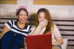 Slaapkamer die van twee de jonge mooie en gelukkige Aziatische Koreaanse studentenmeisjes samen thuis de sociale media van Intern stock afbeeldingen