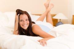 Slaapkamer - het mooie witte bed van vrouwenontwaken Stock Fotografie
