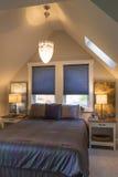 Slaapkamer met bed, bedlijsten, gewelfd plafond, vensterbekledingen en accentverlichting in eigentijds huisbinnenland voor de bet stock foto's