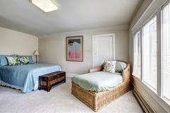 Slaapkamer met bed en rieten sofa royalty-vrije stock afbeelding